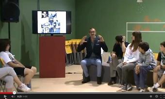 Javier ayudado por una presentación habla a niños sentados en corro