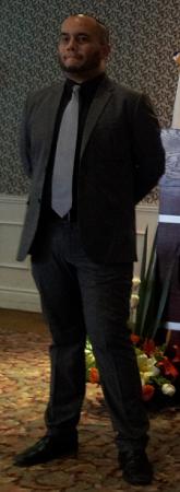 Con traje, corbata gris, barba en parte superior, frente brillante, ojos listos