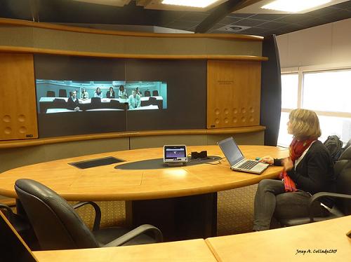 Mesa redonda con una persona viendo una gran pantalla en la que se puede ver una clase con 7 personas