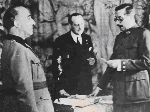 Un militar lee un papel frente a Franco y junto a otra persona en traje civil