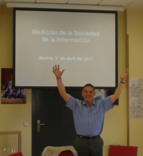 Con los brazos en alto y la diapositiva sobre medición de la sociedad de la información